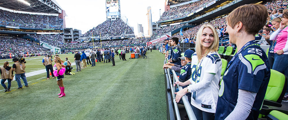 Seahawks fans cheer from the sideline seating