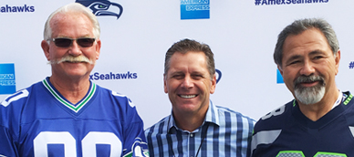 Steve Largent poses for a picture with two Seahawks Fans