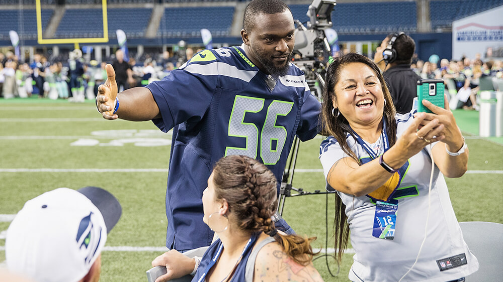 Cliff Avril poses for a picture with fans