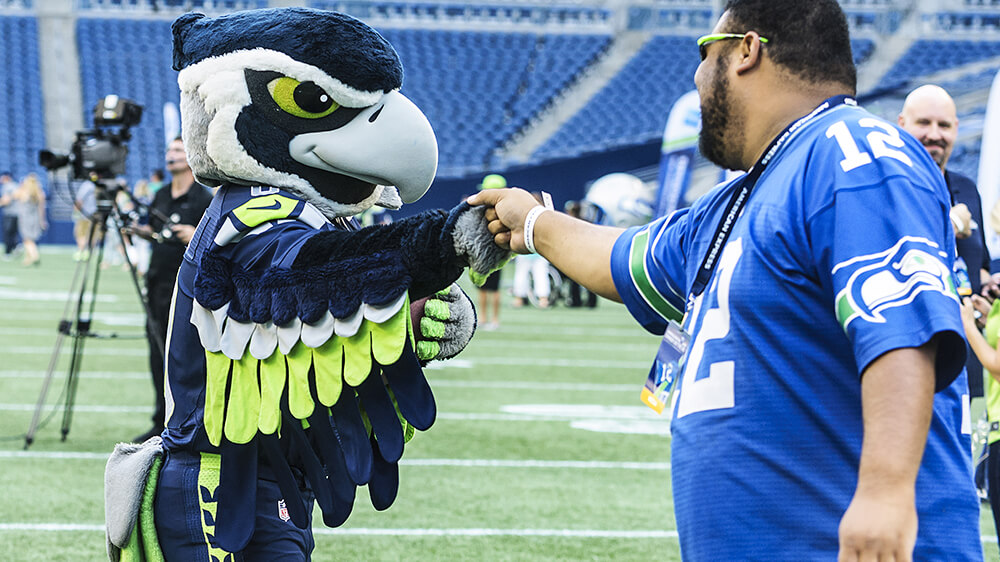 Fan bumps fists with Blitz, the Seahawks mascot