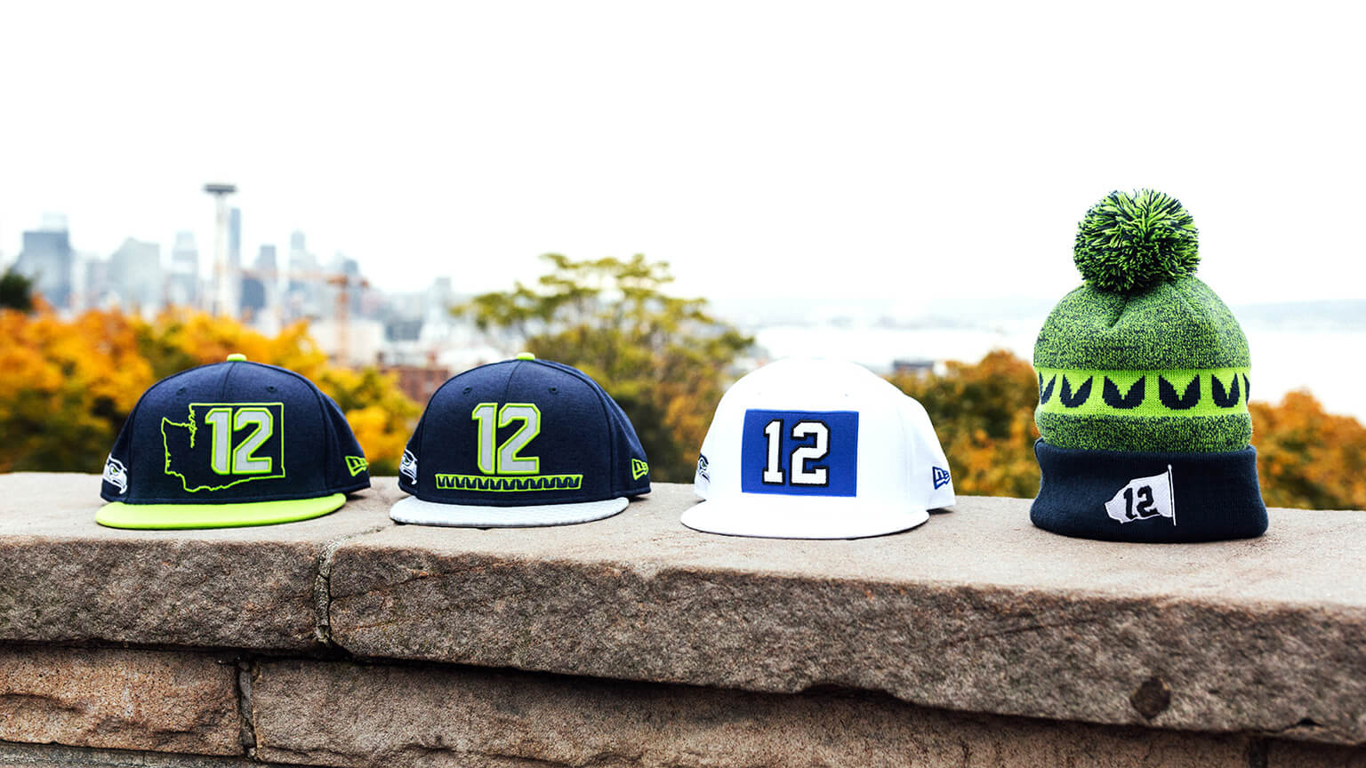 4 New Era hats: blue hat with green bill - Washington state logo outline surrounding the number 12, blue hat with grey bill - 12 logo with feather pattern below, white hat - 12 flag logo, knit hat with pom on top - 12 flag decal in fold up flap